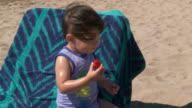 MS Shot of little metis girl eating strawberry at beach / Marbella, Andalusia, Spain