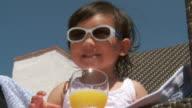 CU LA Shot of little metis girl with sunglasses drinking orange juice / Marbella, Andalusia, Spain