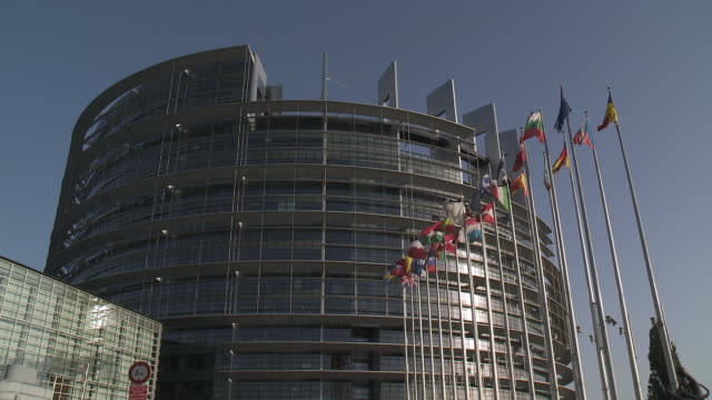 MS Shot of Louise Weiss European Parliament building with flags swaying  on breeze / Strasbourg, Alsace, France