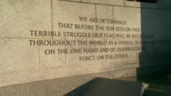 MS PAN shot of low water fountains and quote inscribing in stone and state pillars with Washington Monument with sun shining / Washington, District of Columbia, United States