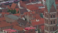 MS AERIAL Shot of Lubeck Cathedral with houses rooftops / Germany