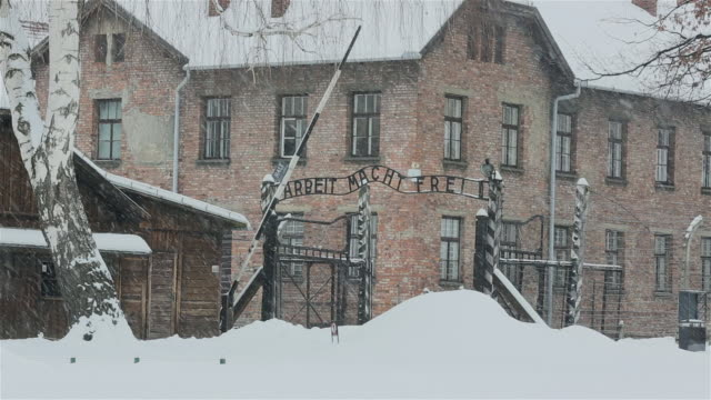 MS Shot of Main entrance gate to Auschwitz with snow rain / Auschwitz-Birkenau, Krakow, Poland