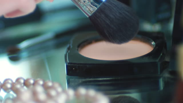 CU SLO MO Shot of make up brush picking up powder / United Kingdom