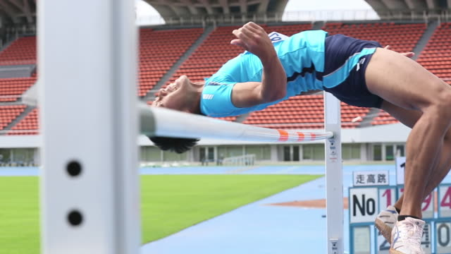 CU Shot of Male high jumper clearing bar / Tokyo, Japan