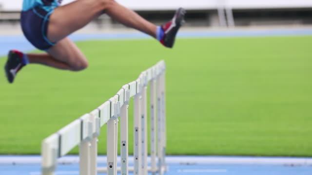 CU Shot of Male runners jumping hurdles in race / Tokyo, Japan