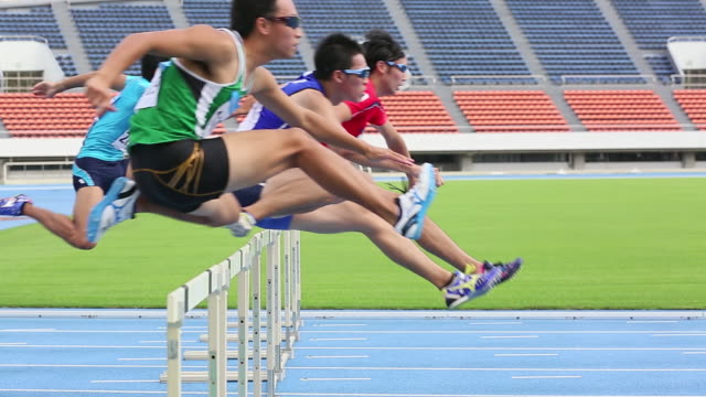 MS Shot of Male runners jumping hurdles in race / Tokyo, Japan