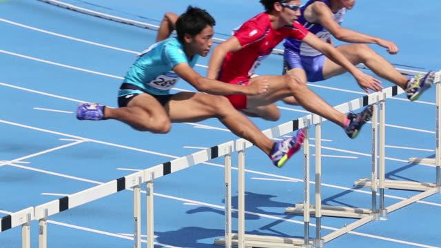MS HA Shot of Male runners jumping hurdles in race / Tokyo, Japan