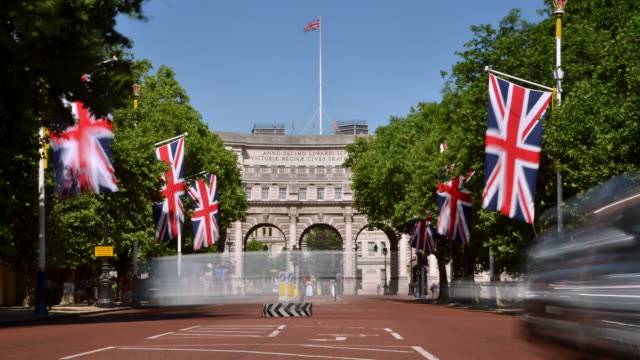 MS T/L Shot of Mall looking towards Admiralty arch in centre line by large Union Jack flags tress and traffic and people / London, Greater London, United Kingdom