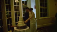 MS Shot of Man and woman cutting cake together at wedding reception / New York, United States