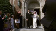 MS TS Shot of Man and woman leave church as people throw confetti at them / New York, United States