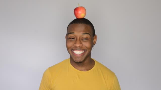 MS Shot of man balancing apple on head / London, Greater London, United Kingdom
