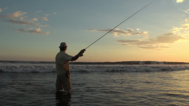 WS Shot of Man casting fly rod in surf at sunset / Iztapa, Guatemala