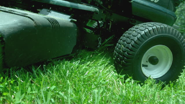 MS SLO MO Shot of man driving lawn tractor mowing lawn / Morristown, New Jersey, United States