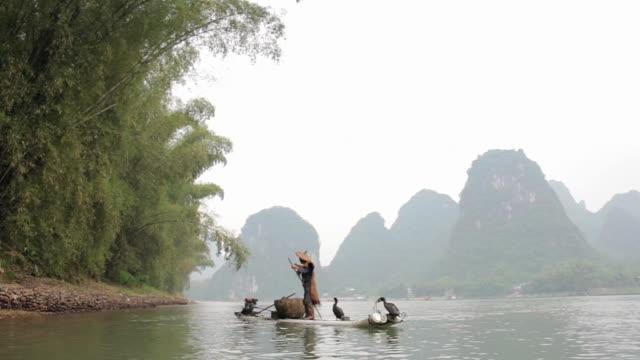 WS Shot of Man fishing with birds and river surroundings / Close to Li River, Guangxi, China