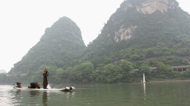WS Shot of Man fishing with birds and surrounded by mountains / Close to Li River, Guangxi, China