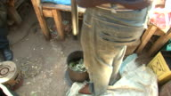 MS Shot of man grinding herbs in Warwick junction herb market / Durban, South Africa