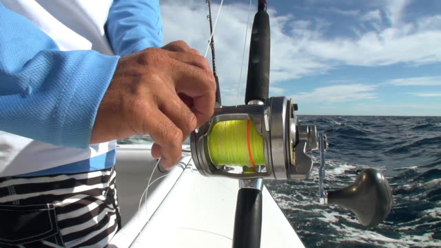 CU Shot of man hands rigging sport fishing rod and reel on ocean / Iztapa, Guatemala