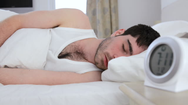 MS Shot of man in bed waking up to alarm clock and then going back to sleep / London, Greater London, United Kingdom
