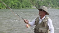 CU SLO MO Shot of man in fishing gear pulling and tossing out line into stream (fly fishing) / Jeongseon, Gangwon do, South Korea