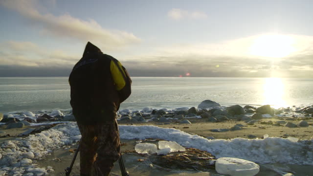 WS Shot of man in snow suit is filming sun set / Arviat, Nunavut, Canada