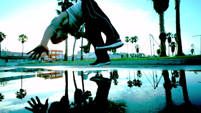 WS SLO MO LA Shot of Man in White running and flips in air and lands in Puddle with Spray / Venice, California, United States