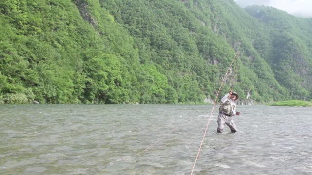 MS SLO MO Shot of man is pulling hard on his rod in Stream / Jeongseon, Gangwon do, South Korea