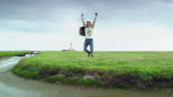 WS Shot of man jumping with joy in front of lighthouse and on green pastures / St. Peter Ording, Schleswig Holstein, Germany