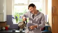 MS Shot of Man making coffee, while talking on phone in kitchen / London, United Kingdom