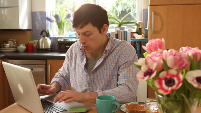 MS Shot of Man making payment with credit card on laptop in kitchen at home / London, United Kingdom