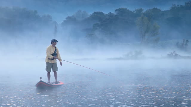MS POV Shot of Man on paddleboard with fly fishing pack and fly rod paddling across misty lake / Lake Atitlan, Guatemala