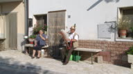 MS Shot of man playing bagpipe seating in front of house / San Polo Matese,Molise, Italy