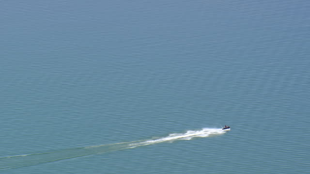 MS AERIAL ZO Shot of man riding motor boat at Boysen Dam / Wyoming, United States