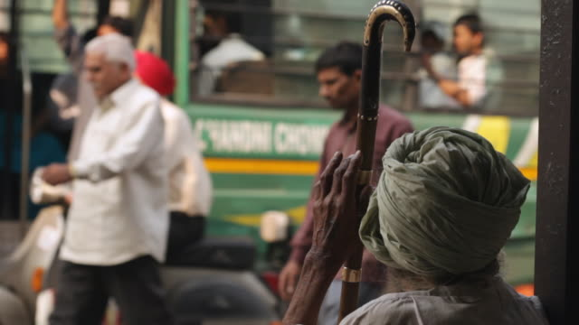 'CU Shot of man sitting with back to busy Indian street / Delhi, National Capital Territory, India'
