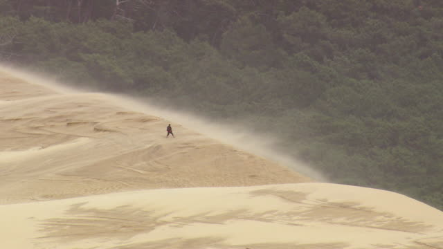 MS AERIAL ZO Shot of man standing in storm at dune du pilat / Aquitaine, France