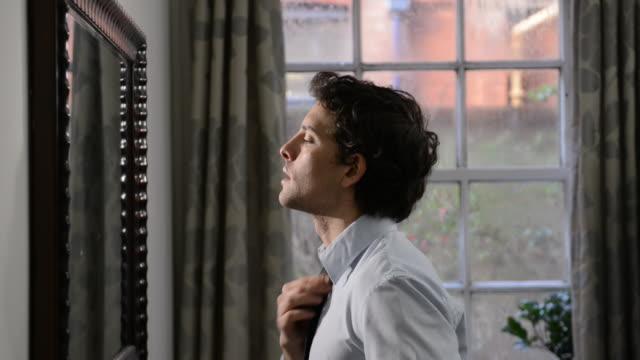 MS Shot of man straightening tie / London, Greater London, United Kingdom