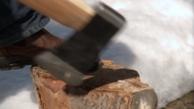 CU Shot of Man using his foot to remove axe from log and chop   log  / Toronto, Ontario, Canada