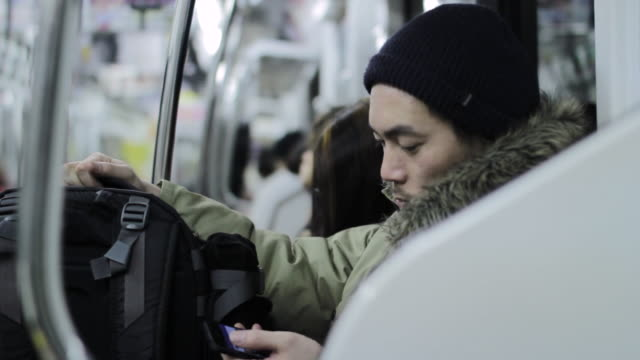MS Shot of man using smartphone in train at night / Shinjuku, Tokyo, Japan
