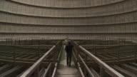 MS Shot of man walking in interior of cooling tower / Charleroi, Hainaut, Belgium