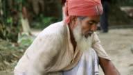 MS Shot of man wearing turban saws off an unseen piece of bamboo pole / Pabna, Bangladesh