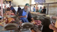 MS Shot of man with cigarrate in mouth cutting meat in market / Tolagnaro, Madagascar
