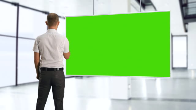 MS Shot of Man with green screen and remote control / Bergen, Hordaland, Norway