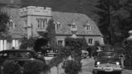 MS Shot of mansion exterior with period cars parked out in front and people dressing in formal attire get into cars and drive away