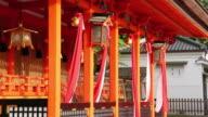 MS Shot of many Japanese Shinto shrine style Suzu with large bells hung over entrance of shrine / Fushimi ku, Kyoto, Japan.