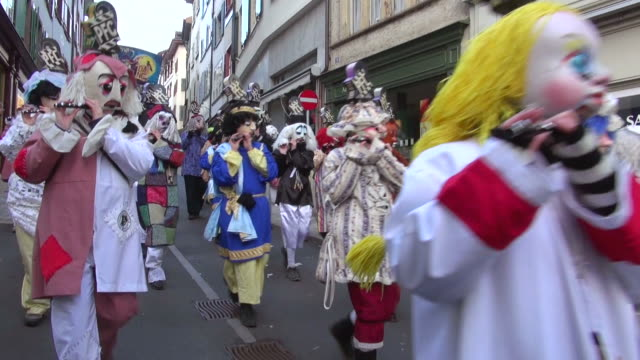 MS Shot of masked people walking on street and celebrating in Basel Carnival (Basler Fasnacht) / Basel, Switzerland