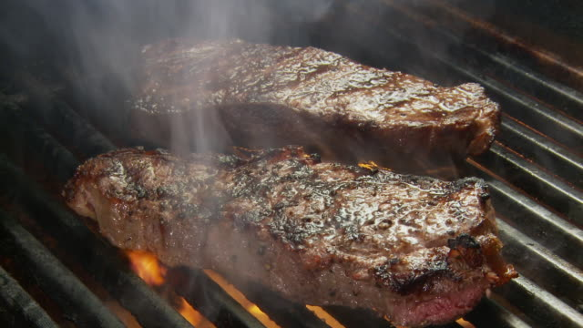 CU Shot of  meat grilling steaks with flame and smoke / Atlanta, GA, United States