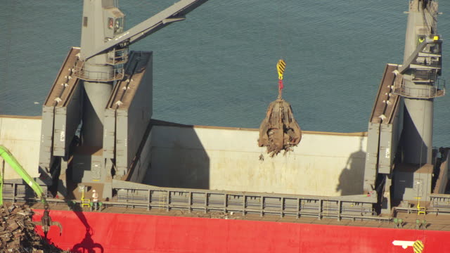 MS AERIAL Shot of mechanical arm lifting trash onto red barge in Port of Tampa / Port of Tampa, Florida, United States