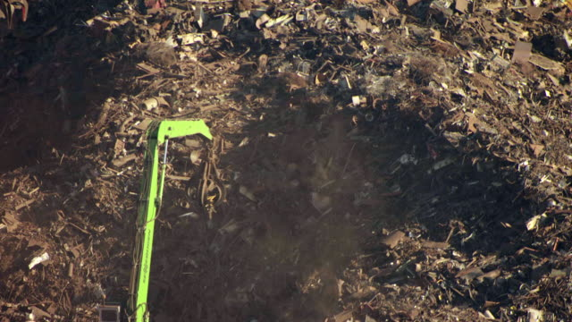 MS AERIAL TS Shot of mechanical arm moving around trash in large pile / Port of Tampa, Florida, United States