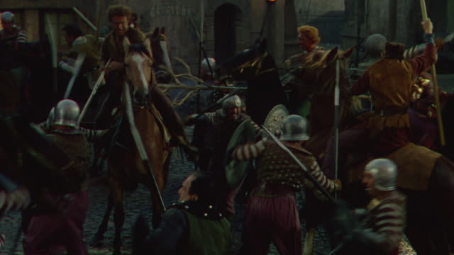 MS PAN Shot of medieval battle raging in court yard of castle and some men on horseback