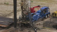 CU AERIAL TS Shot of Men working at base of oil well tower to reveal entire tower in Natrona County / Wyoming, United States