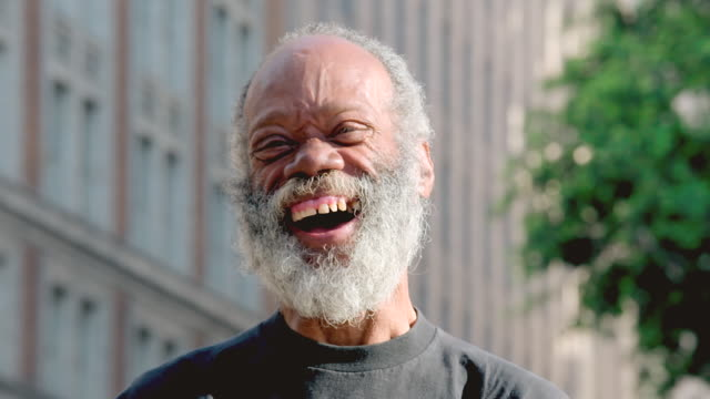 CU Shot of middle aged bearded man smiling, then laughing hard and genuinely and his eyes are wise and joyful / Los Angeles, California, United States